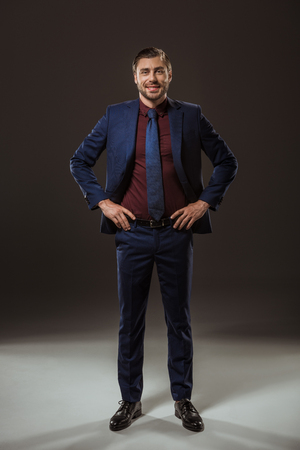full length view of handsome businessman standing with hands on waist and smiling at camera on black