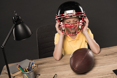 smiling schoolboy putting on american football helmet at table with ball, lamp, colour pencils and books on grey background Standard-Bild - 105988168