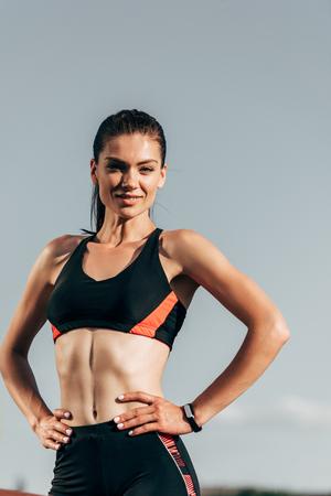 beautiful athletic woman in sports bra posing against blue sky