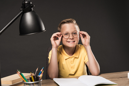 smiling schoolboy adjusting eyeglasses and sitting at table with lamp, colour pencils, books and textbook on grey background 免版税图像