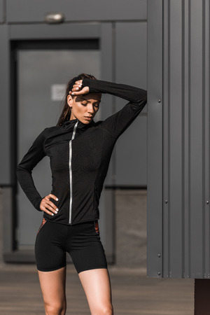 tired young sportswoman in sportswear in city