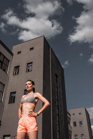 beautiful young sportswoman in sportswear in city