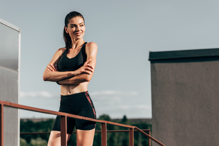 attractive confident sportswoman with crossed arms posing on roof Stock fotó