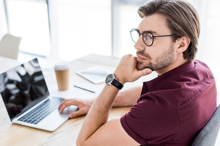 pensive handsome businessman working on startup project in office and looking away Stock Photo