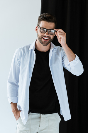 Stylish young man smiling and wearing glasses standing by black curtain