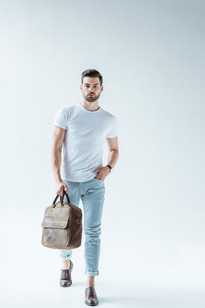 Homme confiant à la mode portant une mallette sur fond blanc