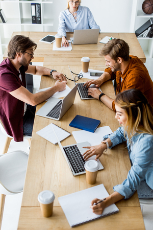 high angle view of young multicultural colleagues working on startup project in office with gadgets Stock Photo