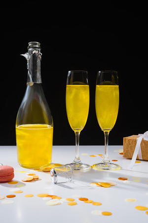 close up view of bottle and glasses of yellow champagne, macaron and gift on surface on black background