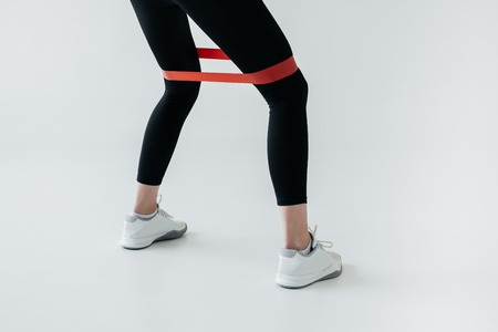 partial view of exercising with rubber tape on grey background Foto de archivo