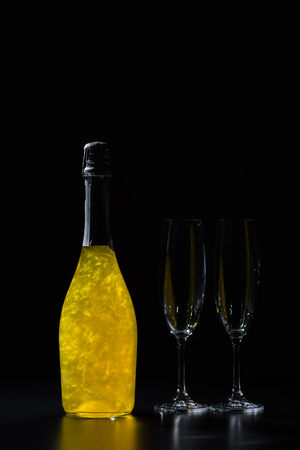 close up view of bottle of champagne and empty glasses on black background Stockfoto