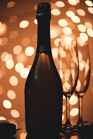 close up view of bottle of champagne and empty glasses on tabletop in bokeh style