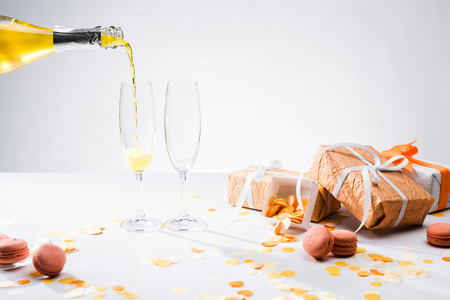 close up view of pouring yellow champagne into glasses process, macarons and arranged gifts on grey backdrop 版權商用圖片