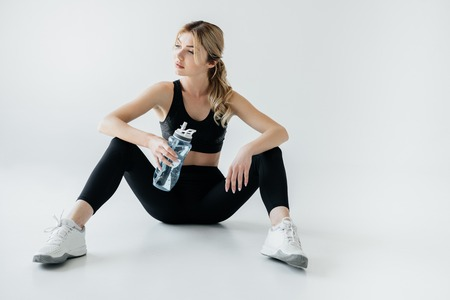 athletic woman in black sportswear with sportive water bottle isolated on grey