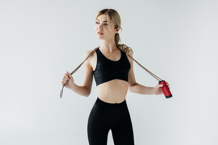 portrait of young sportive woman with skipping rope isolated on grey 写真素材