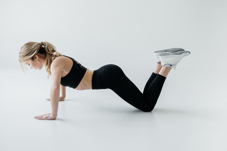 side view of young sportswoman doing push ups isolated on grey Stock Photo