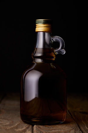 bottle of olive oil on wooden table on black background Stock Photo