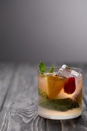 glass of lemonade with ice cubes, mint leaves, pineapple and strawberry