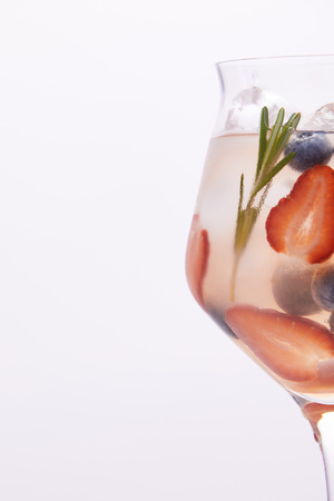 partial view of glass of lemonade with rosemary, blueberries and strawberries isolated on white background Stock Photo