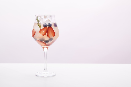 glass of lemonade with rosemary, blueberries and strawberries on purple background