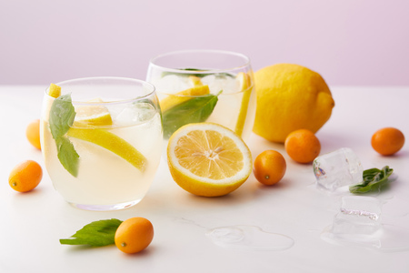 two glasses of lemonade with mint leaves, ice cubes and lemon slices surrounded by kumquats and lemons on purple background Stock Photo