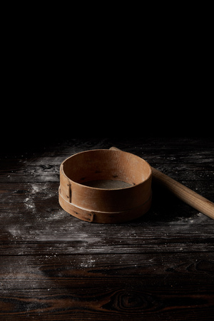 close up view of sieve and rolling pin on wooden table covering by flour isolated on black background 스톡 콘텐츠