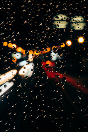 Close up view of raindrops on window and bokeh city lights on background 版權商用圖片