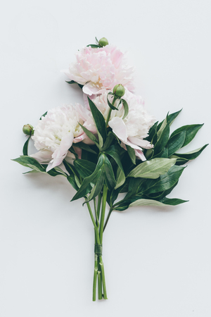top view of beautiful light pink peonies with leaves on white