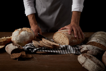 cropped image of baker in apron cutting bread on sackcloth on wooden table