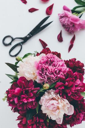 top view of light pink peony bouquet with scissors on white Zdjęcie Seryjne