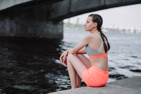 attractive young athletic woman in sportswear sitting on quay