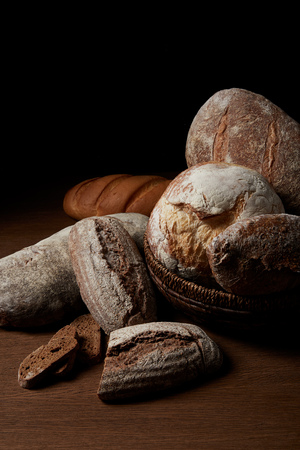 closeup shot of various types of bread and wicker breadbasket on wooden table