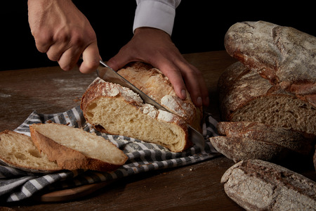 cropped shot of male baker cutting bread by knife on sackcloth on wooden table