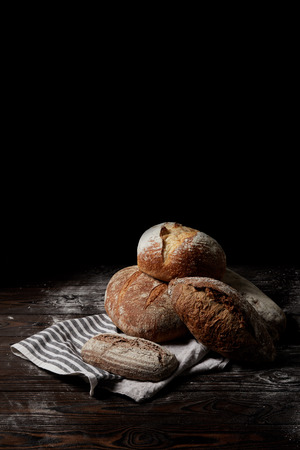 closeup view of various types of bread and sackcloth on wooden table covering by flour isolated on black background Reklamní fotografie