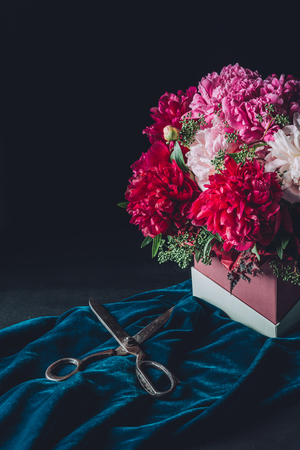 floristry bouquet of beautiful pink peonies with scissors on dark background Zdjęcie Seryjne