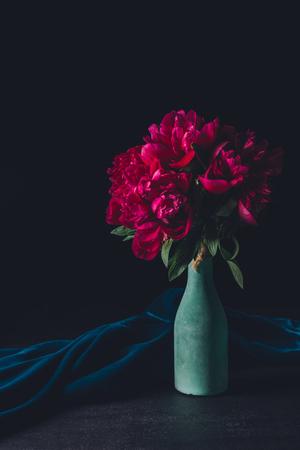 bouquet of pink peonies in vase on dark background
