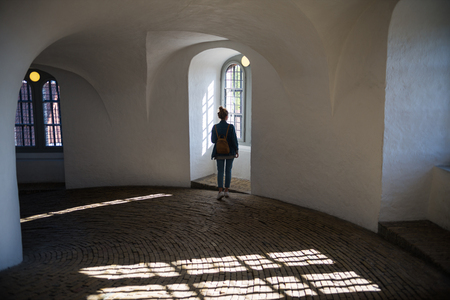back view of young woman standing in beautiful historical building and looking at window, Interior of the Round Tower
