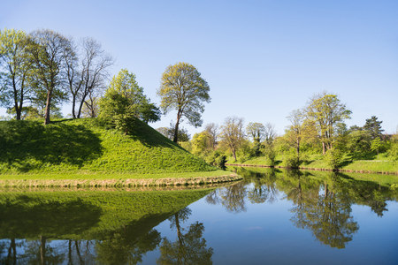 beautiful green hills, trees and bushes reflected in water, copenhagen, denmark