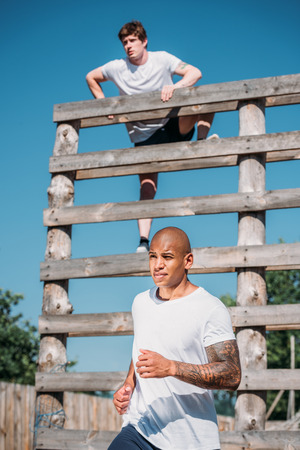 selective focus of young interracial soldiers practicing in obstacle run on range