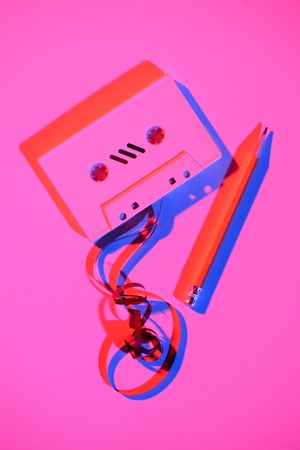toned pink picture of retro audio cassette with pencil and tape Stock Photo