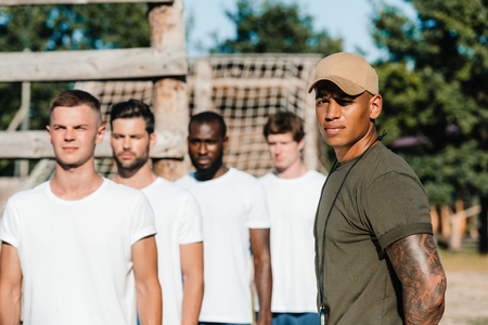 selective focus of african american tactical instructor and interracial soldiers on range