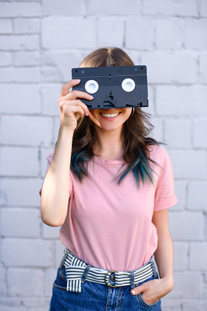 obscured view of smiling woman covering eyes with retro video cassette in hand against white brick wall
