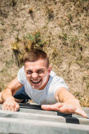 overhead view of young soldier climbing wooden barrier during obstacle run on range