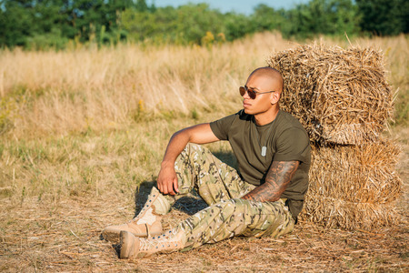 young african american soldier in military uniform and sunglasses resting near hay on range