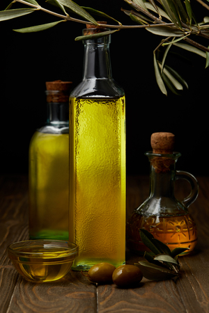bottles of various olive oil on wooden surface