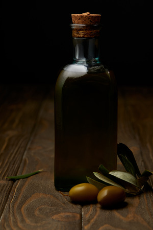 bottle of tasty olive oil with branch on wooden surface