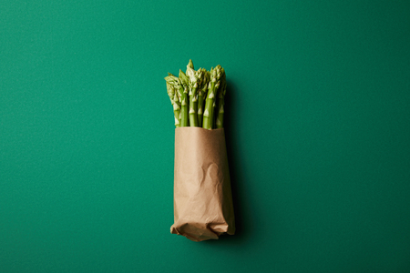 top view of bunch of ripe asparagus covered with kraft paper on green surface Reklamní fotografie