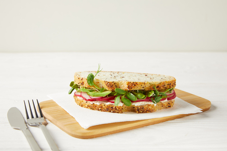 delicious sandwich with radish slices and pea shoots on wooden cutting board Фото со стока