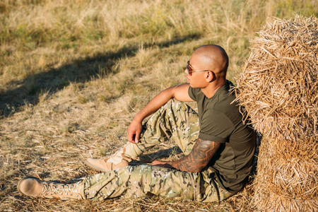 side view of young african american soldier in military uniform and sunglasses resting near hay on range