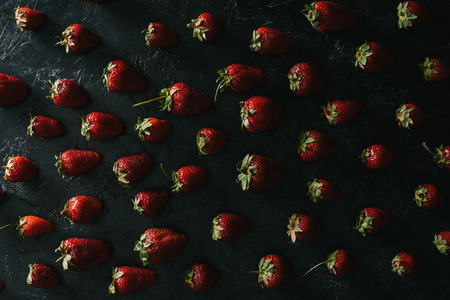 top view of ripe summer strawberries on dark background