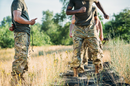 partial view of tactical instructor with stop watch and interracial soldiers practicing with tires on ground on range Stock Photo
